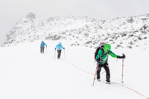 Rope team in a storm during the ascent of Mt Schwarzensteinの写真素材 [FYI02340699]