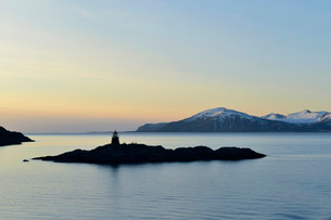 Silhouette of a small island with a lighthouse in theの写真素材 [FYI02340727]