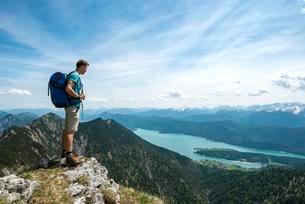 Hiker at Heimgarten, view from the top with Walchensee andの写真素材 [FYI02340871]