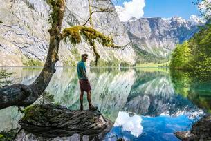 Young man standing on stone in water, reflection in lakeの写真素材 [FYI02341023]