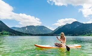 Young woman sitting on a Standup-Paddle Board or SUPの写真素材 [FYI02341223]