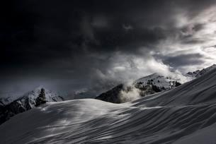 Snowy mountain landscape, dramatic light with dark cloudsの写真素材 [FYI02341245]