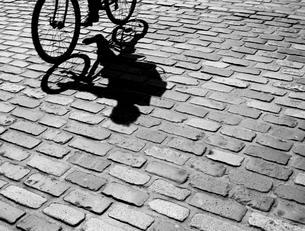 Silhouette and shadow of a cyclist on cobblestonesの写真素材 [FYI02341399]
