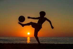 Boy with soccer ball, sunset at the sea, beach, Italyの写真素材 [FYI02341425]