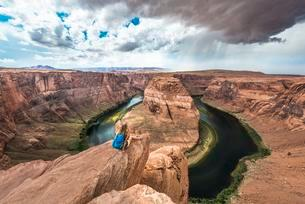 Tourist siting on a rock, looking over the Horseshoe Bendの写真素材 [FYI02341492]