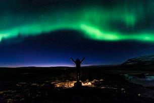 Young woman stretching arms upwards, starry sky, northernの写真素材 [FYI02341713]