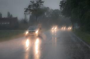 Dangerous car drive in heavy rain, dazzling headlights inの写真素材 [FYI02341903]