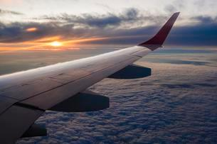 Wing of the airplane, flight over cloud cover, sunsetの写真素材 [FYI02342321]