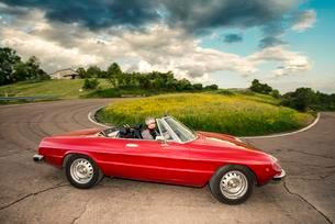 Red Alfa Spider 2000, convertible on winding road, atの写真素材 [FYI02343111]