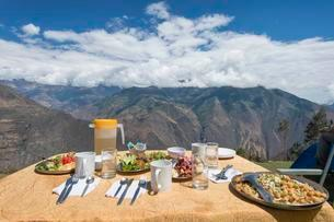 Covered table with dinner in front of mountain panoramaの写真素材 [FYI02343214]