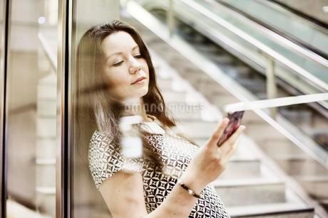 Young woman posing with smartphone behind a glass wall in aの写真素材 [FYI02343411]