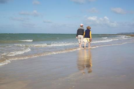Elderly couple walks barefoot through the water on theの写真素材 [FYI02343429]