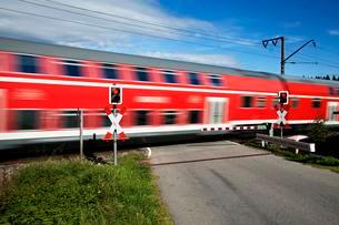 Level crossing with passing train, Andraskreuzの写真素材 [FYI02343504]