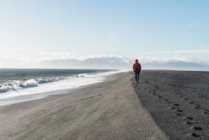 Man walking by the sea in the black sandy beach, lavaの写真素材 [FYI02343692]