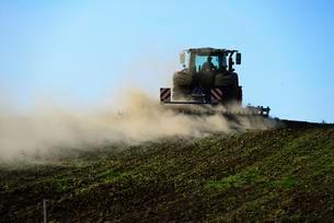 Farmer harrows field with tractor, Franconian Switzerlandの写真素材 [FYI02343697]