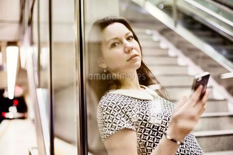 Young woman posing with smartphone behind a glass wall in aの写真素材 [FYI02343715]