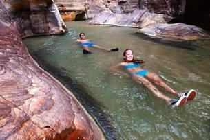 Young couple floats at the canyon of Wadi Mujib, Jordanの写真素材 [FYI02343817]