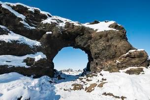 Natural arch, view of a snowy landscape, lava field coveredの写真素材 [FYI02343819]