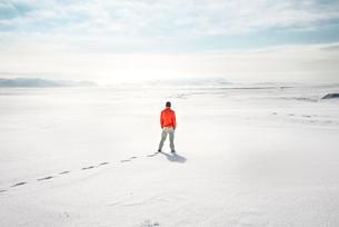 Young man stands alone in snowy landscape, snowy lavaの写真素材 [FYI02343820]