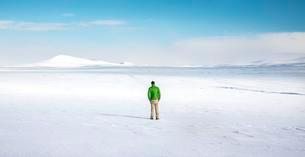 Young man stands alone in snowy landscape, snowy lavaの写真素材 [FYI02343822]