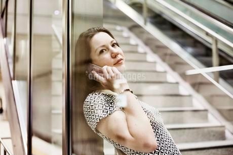 Young woman posing with smartphone behind a glass wall inの写真素材 [FYI02343831]