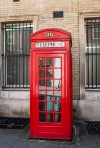 Young man in a red phone booth, London, England, Greatの写真素材 [FYI02343846]