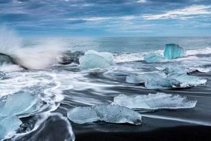 Pieces of ice on the black beach lapped by the sea, atの写真素材 [FYI02344005]