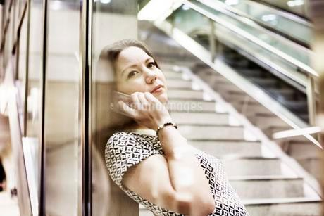 Young woman posing with smartphone behind a glass wall in aの写真素材 [FYI02344049]