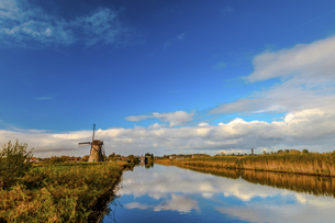 Windmill against the sky and river; Kinderdijk; Nederlandの写真素材 [FYI02344598]