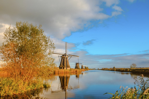 Windmill against the sky and river; Kinderdijk; Nederlandの写真素材 [FYI02344826]