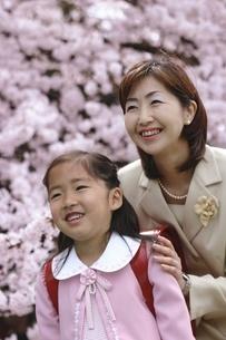 桜の木と小学生少女と母親の写真素材 [FYI02354242]