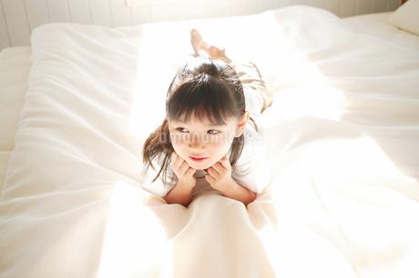 ベッドに寝る子の写真素材 [FYI02354243]