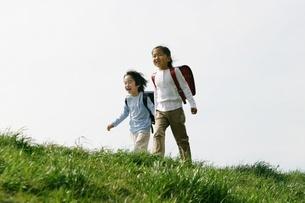 土手を歩くランドセルを背負った少女2人の写真素材 [FYI02354266]