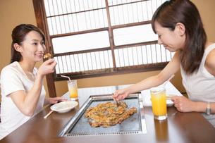 もんじゃ焼きを食べる女性の写真素材 [FYI02354412]