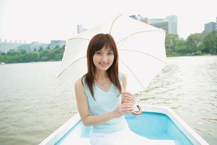 ボートの上で日傘をさした女性の写真素材 [FYI02354503]