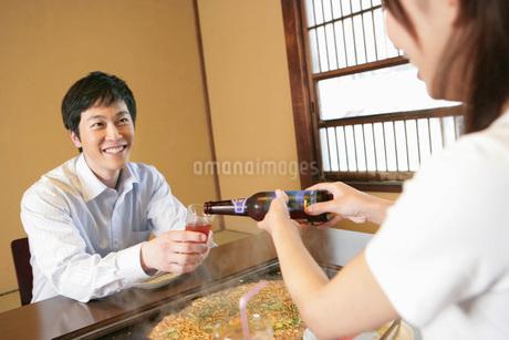 もんじゃ焼きを食べるカップルの写真素材 [FYI02354550]