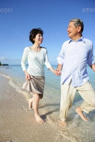 浜辺を走るシニアカップルの写真素材 [FYI02354574]
