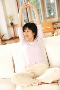 ソファの上で伸びをする女性の写真素材 [FYI02354591]
