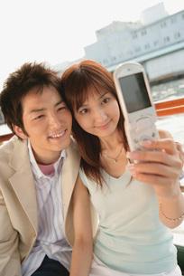 写真を撮るカップルの写真素材 [FYI02354592]