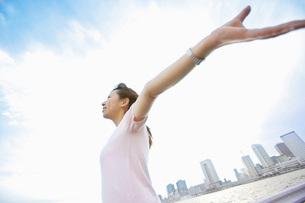 風を受けて伸びをする女性の写真素材 [FYI02354622]