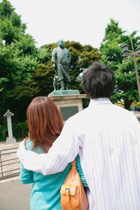 肩を組むカップルと銅像の写真素材 [FYI02354628]