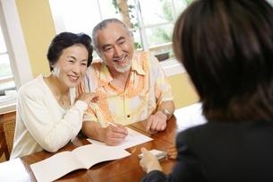 営業マンと話すシニア夫婦の写真素材 [FYI02354668]