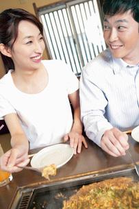 もんじゃ焼きを食べるカップルの写真素材 [FYI02354729]