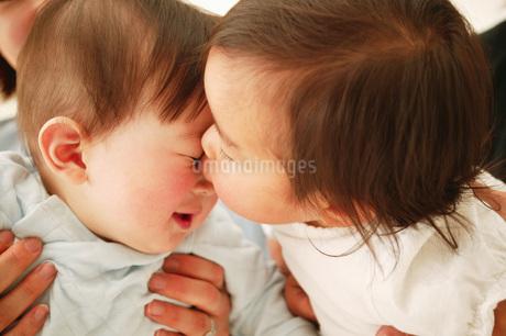 子供にキスをされる赤ちゃんの写真素材 [FYI02354811]