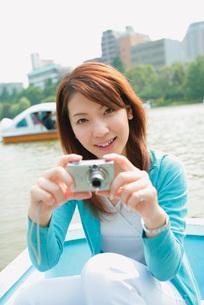 ボートに乗って写真を撮る女性の写真素材 [FYI02354823]