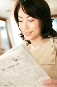 新聞を読む女性の写真素材 [FYI02354824]