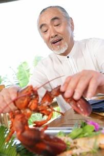 ロブスターを食べるシニア男性の写真素材 [FYI02354918]