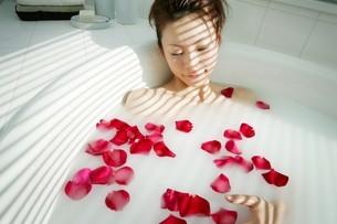 バラの花弁を浮かべた湯船に浸かる女性の写真素材 [FYI02354970]