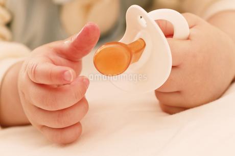 おしゃぶりを持った赤ちゃんの手の写真素材 [FYI02355084]
