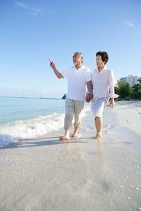 浜辺を歩くシニアカップルの写真素材 [FYI02355096]